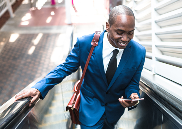 Man riding up escalator, holding a mobile phone